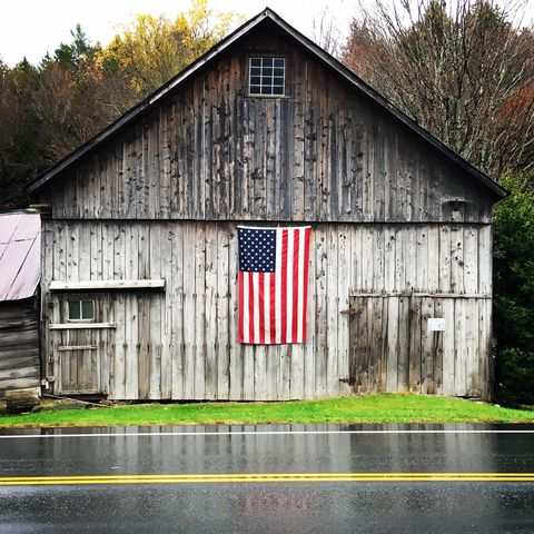 American flag on wooden house by wet road