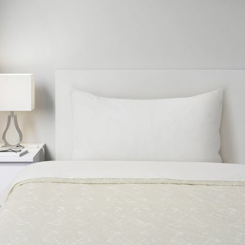 a bed frame with sheets and side table