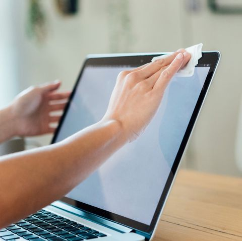 Cropped shot of woman cleaning the surface of the laptop with a cleaning wipe