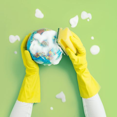 hand with protective rubber glove cleaning a globe model with soap and cleaning sponge on green background